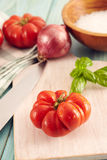 Corleone Tomato. Tomatoes corleone type for sauce on a aqua wooden table with basil and onion Royalty Free Stock Photos