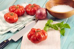 Corleone Tomato. Tomatoes corleone type for sauce on a aqua wooden table with basil and onion Royalty Free Stock Images