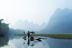 Cormorant, fish man and Li River scenery sight with fog in sprin Royalty Free Stock Image