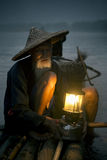 Cormorant fisherman with his bird. Cormorant fisherman with his latern light in the river during sunset stock images