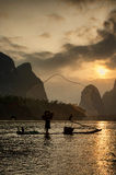 Cormorant fisherman with his bird. Throwing net in the river during sunset royalty free stock photography