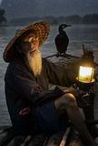 Cormorant fisherman with his bird. Very old cormorant fisherman with his bird and latern light at the river royalty free stock photo