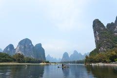 Cormorant, homme de poissons et vue de paysage de Li River avec le brouillard dans le sprin Image libre de droits