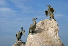 Cormorant sculpture on rock Stock Photo