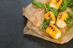 Corn baked in olive oil, with pepper, salt and basil on blue dis Royalty Free Stock Photo