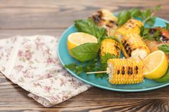 Corn baked in olive oil, on a wooden surface. Vegetarian, vegan Stock Image