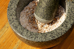 Corn being grinded with mortar and pestle Stock Images