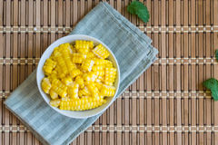 Corn Boil a cup of white bands on the bamboo floor. Royalty Free Stock Photography