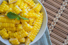 Corn Boil a cup of white bands on the bamboo floor. Stock Image