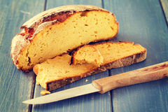 Corn bread with knife on blue background Royalty Free Stock Photo