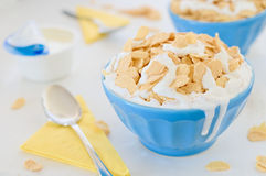 Corn cereals with greek yogurt in blue ceramic pot. Cornflake cereals with greek yogurt in blue ceramic pot and two drips on the side with open yogurt and yellow Stock Photography