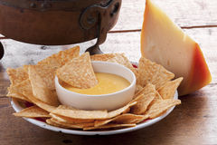 Corn chips and cheese sauce. On wooden table Stock Images