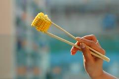 Corn on chopsticks. A fun shot of corn on chopsticks stock image