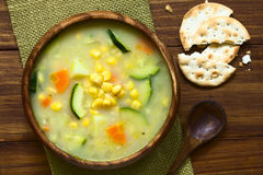 Corn Chowder. Vegetarian corn and courgette chowder served in wooden bowl, saltine cracker and wooden spoon on the side, photographed overhead on dark wood with Royalty Free Stock Photos