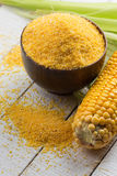Corn cob amd corn meal on wooden background Royalty Free Stock Images