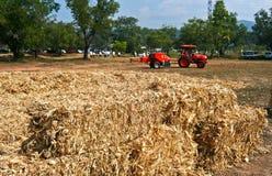 Corn cob briquette and tractor orange color Royalty Free Stock Photo