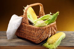 Corn on the cob and a linen napkin in a basket. Stock Photo