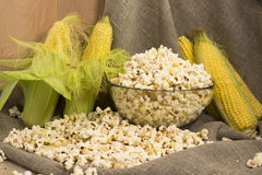 Corn on the cob and popcorn in a glass bowl on the table Royalty Free Stock Image