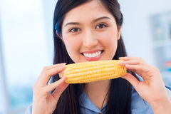 Corn cob. Portrait of a happy Asian girl holding an appetizing corn cob Royalty Free Stock Image