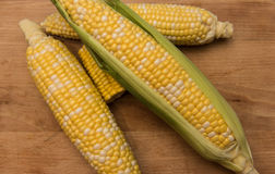 Corn on the cob on a wooden background. Corn on the cob sitting on a wooden cutting board Royalty Free Stock Photos