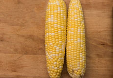 Corn on the cob on a wooden background. Two corns on the cob sitting on a wooden cutting board Royalty Free Stock Images