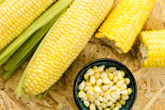 Corn cobs and a bowl of kernels, on wooden surface Stock Photography