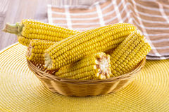 Corn cobs close-up in wicker basket background of yellow wicker Stock Images
