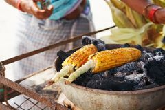 Corn cobs on the grill. Close-up image with corns and hands. Asian, Indian and Chinese street food. Trolley on the beach. GOA stock images