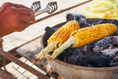 Corn cobs on the grill. Close-up image with corns and hands. Asian, Indian and Chinese street food. Trolley on the beach. GOA stock photography