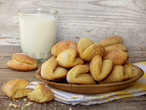 Corn cookies in a basket and a glass of milk. On wooden background royalty free stock images
