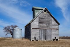 Corn Crib and Silo. This is an early Spring picture of a corn crib and a small metal silo in the middle of a corn field near Streator, Illinois. This picture was royalty free stock photos
