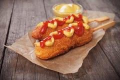 Corn dog with mustard and ketchup. Corn dog, fried sausage in batter with mustard and ketchup Stock Images