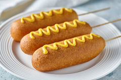 Corn dog traditional American corndog street junk food deep fried hotdog meat sausage snack with mustard on top Stock Photos