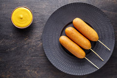 Corn dog traditional American corndog street junk food deep fried hotdog meat sausage snack treat on stick Stock Photo
