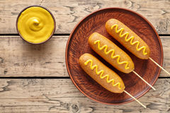 Corn dog traditional American corndog street junk food deep fried hotdog meat sausage snack with yellow mustard. Corn dog traditional American corndog street Stock Photography
