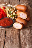 Corn dogs, french fries and ketchup on the table. Vertical royalty free stock image