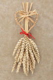 Corn Dolly. With red bow over old brown paper background Stock Photos