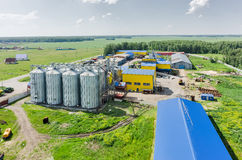 Corn dryer silos standing in a field of corn Stock Images