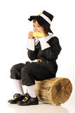 Corn-Eating Pilgrim. An adorable preschool-aged Pilgrim eating an ear of corn while sitting on an old log Royalty Free Stock Images