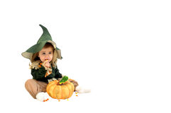 Corn eating Scarecrow. Tiny scarecrow sits in an all white room and chows down on candy corn.  A single pumpkin sits in front this adorable little girl Royalty Free Stock Photography