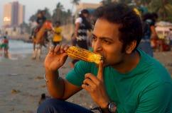 Corn enjoyment. A young Indian man enjoying a baked and hot corn maize on a beach Royalty Free Stock Photos
