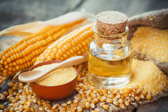 Corn essential oil bottle, corn groats, dry seeds and corncobs royalty free stock photos