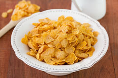 Corn flake in white dish. On brown background Royalty Free Stock Images
