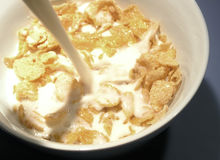 Corn flakes. Pourring milk in a bowl with cornflakes Royalty Free Stock Images