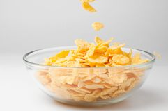 Corn flakes. Closeup of a bowl with pouring cereal flakes Royalty Free Stock Photos
