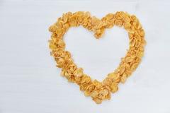 Corn-Flakes auf einem gemalten weißen hölzernen Hintergrund Das Symbol des Herzens wird von den Corn-Flakes ausgebreitet stockfoto