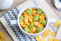 Corn flakes with avocado. And jug of milk royalty free stock images