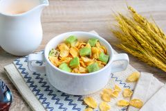 Corn flakes with avocado. And jug of milk royalty free stock photography