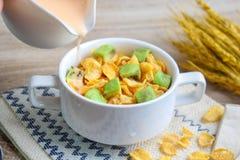 Corn flakes with avocado. And jug of milk stock photos