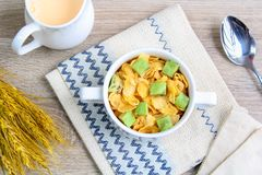 Corn flakes with avocado. And jug of milk stock images